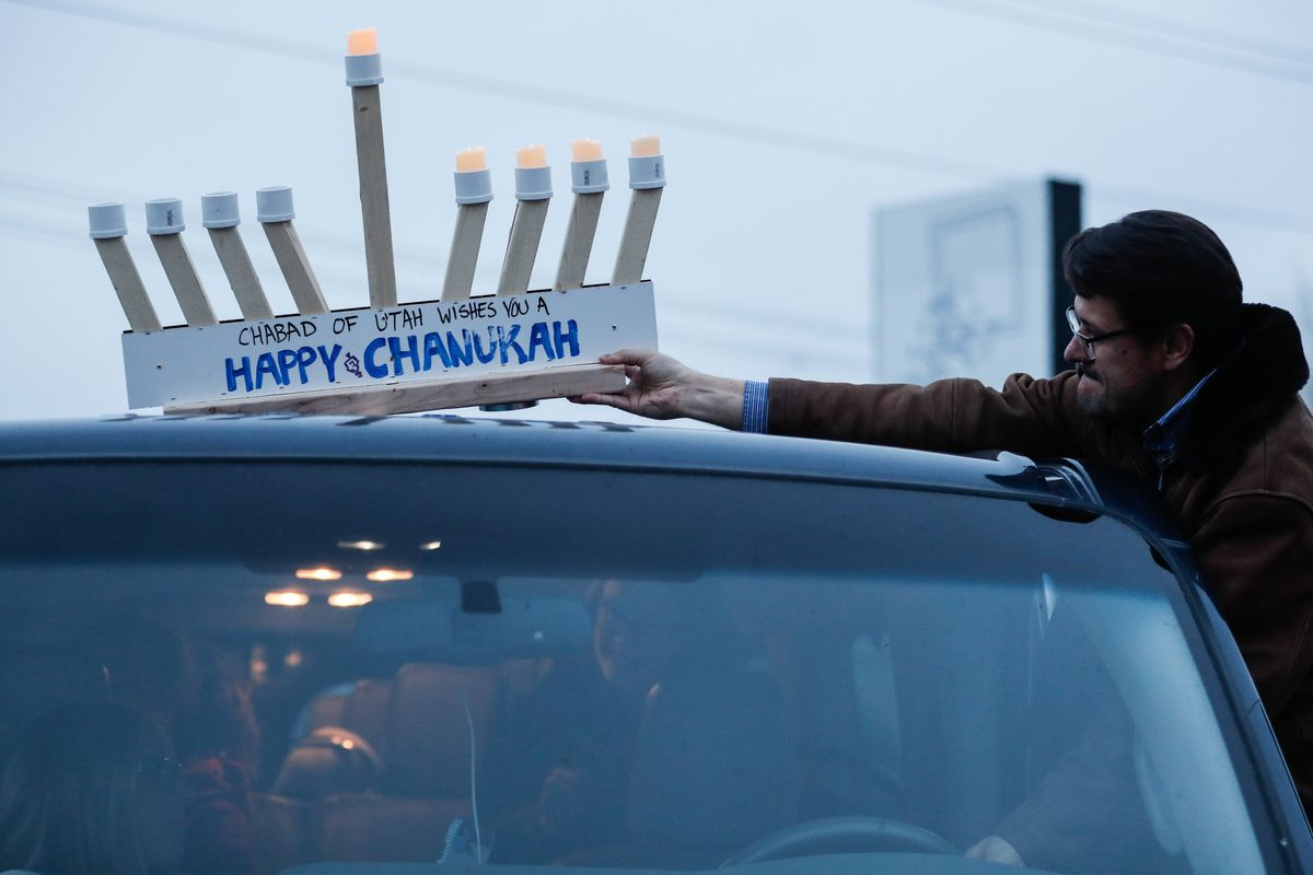 John Sablana affixes a menorah to the roof of his vehicle before a Hanukkah parade through Salt Lake City on Sunday, Dec. 13, 2020. The event was organized byChabad Lubavitch of Utah.