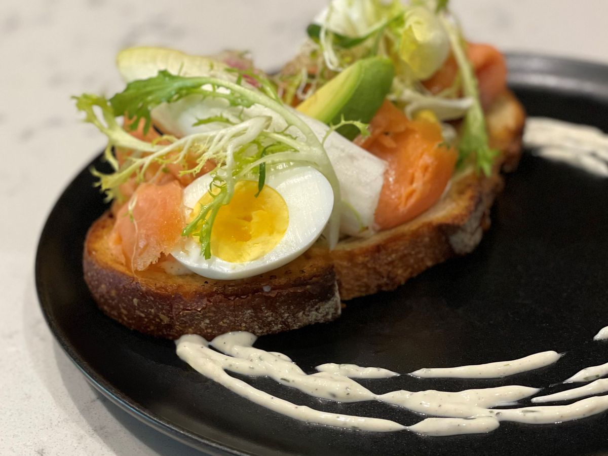 A plate of toast topped with smoked salmon, hardboiled eggs and greens.