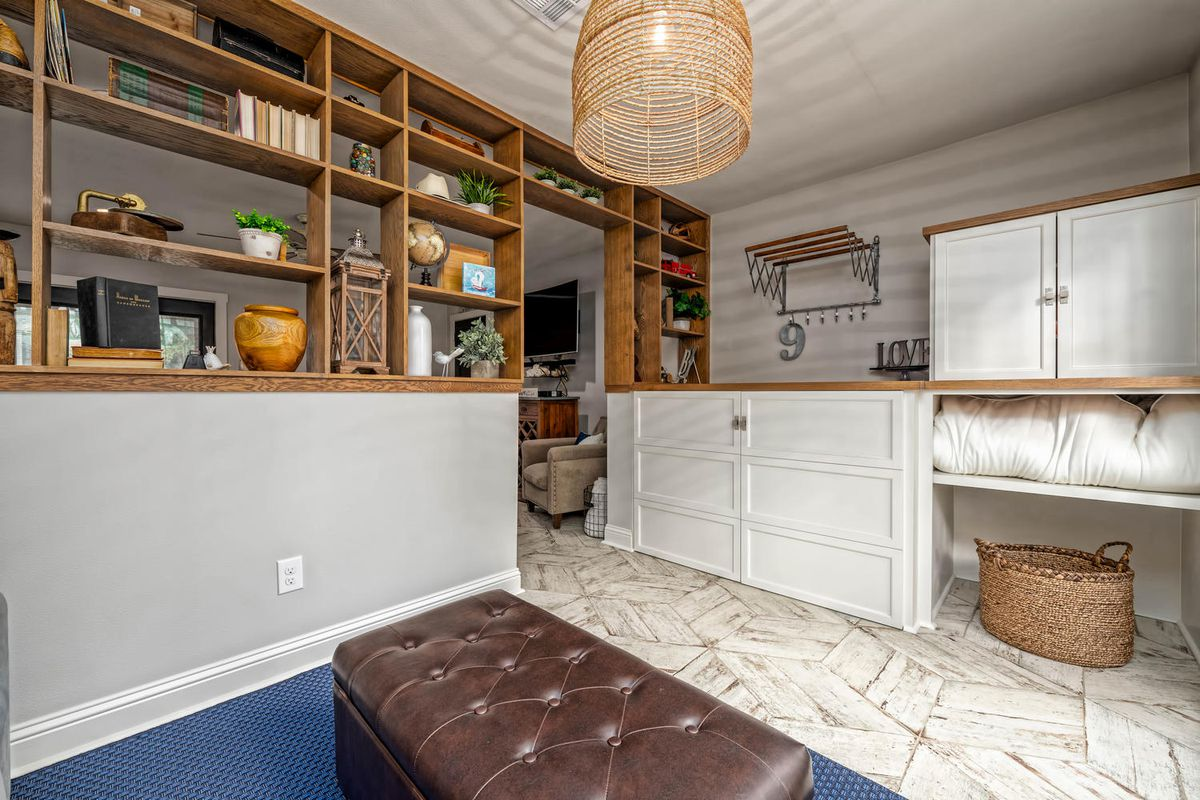 A mud room has open shelving on one side, white cabinets, and a basket.