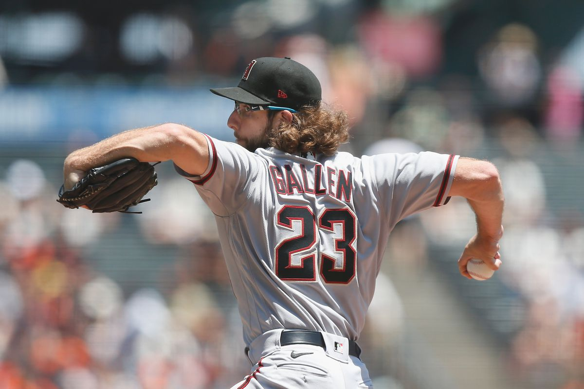 Zac Gallen's luscious locks flow out behind him mid windup as he throws a pitch with the backdrop of Oracle Park