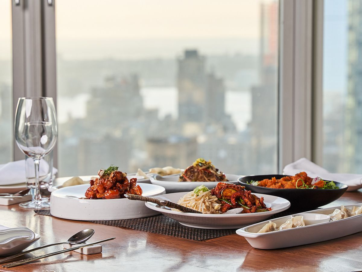 Four dishes and a glass of wine are set on a table, with a window offering views of the New York City skyline in the background