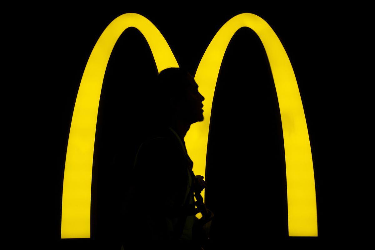 A pedestrian walks past an American fast-food hamburger...