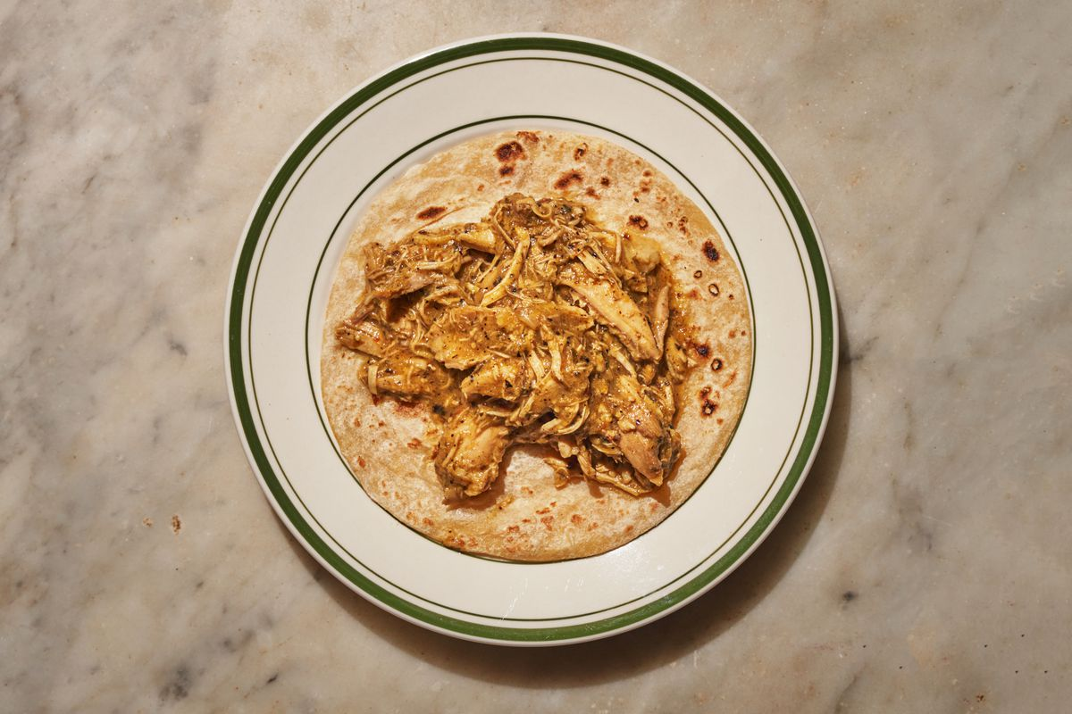 An overhead photograph of a flour tortilla on a plate with pulled chicken meat