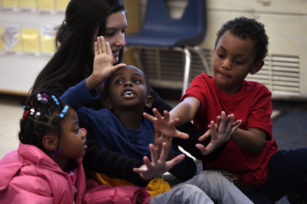 Paraprofessional Madison Marasco counts to 10 with kindergarten students Salah Osman, Za'Mayah Jones, and Deangelio Heard at Denver's Fairview Elementary.