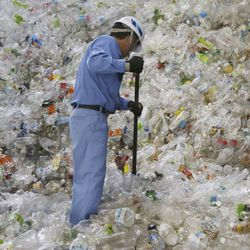 In this June 18, 2019, photo, a plastic recycling company worker sorts out plastic bottles collected for processing at Tokyo Petbottle Recycle Co., Ltd, in Tokyo. Japan has a plastic problem. Single bananas here are sometimes wrapped in plastic. So are individual pieces of vegetables, fruit, pastries, pens and cosmetics. Plastic-wrapped plastic spoons come with every ice cream cup.