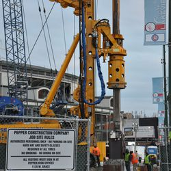 Steel beam being pushed into the ground on the Clark Street side of the triangle lot
