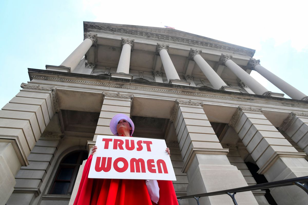 "An abortion activist with the Handmaids Coalition of Georgia stands outside the Georgia Capitol building holding a sign that reads, ""Trust women."""