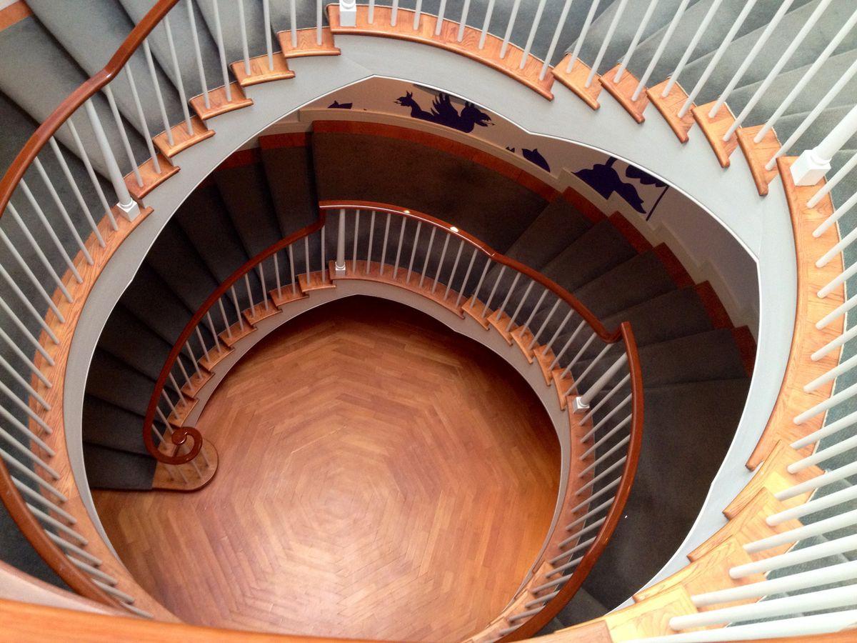 A bird's-eye photo of a circular staircase in a museum.