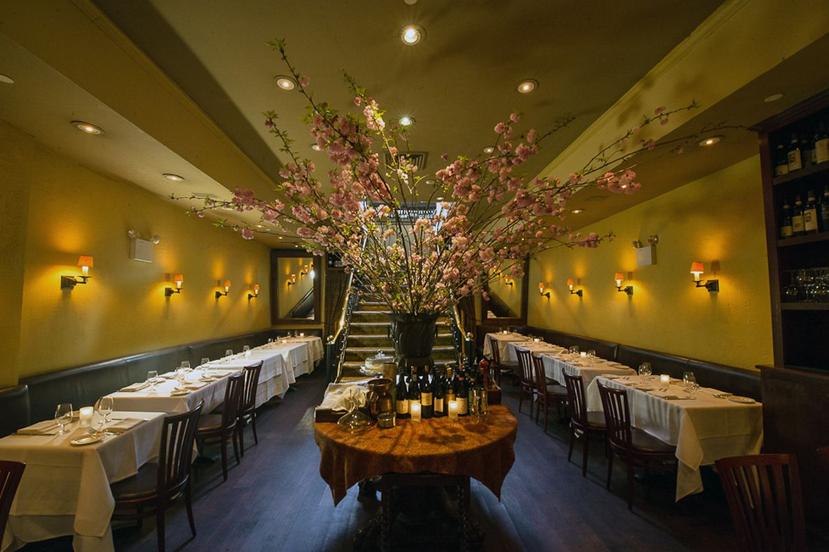 A tall flower arrangement sits in the middle of Babbo's dining room