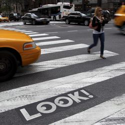 """Pedestrians and traffic move past a """"Look!"""" sign on the crosswalk at the intersection of 42nd St. and 2nd Ave. in New York, Thursday, Sept. 20, 2012.  Crossing the street in New York City is complicated: Even when it's one-way, you should look both ways, and stop texting for a few seconds.  That's what city transportation officials tell pedestrians who often miss getting hit in the chaotic every-which-way-including-loose mill of vehicles, bicycles, scooters and sometimes, carriage horses.  They're making their point visible with """"LOOK!"""" signs stenciled at 110 of the most dangerous intersections in the city's five boroughs."""