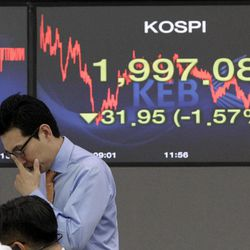 A currency trader works in front of the screen showing the Korea Composite Stock Price Index at the foreign exchange dealing room of the Korea Exchange Bank headquarters in Seoul, South Korea, Monday, April 9, 2012. Asian stock markets declined Monday after U.S. hiring slowed in March, raising doubts about the durability of the recovery in the world's No. 1 economy. The Korea Composite Stock Price Index fell 1.57 percent, or 31.95, to close at 1,997.08.