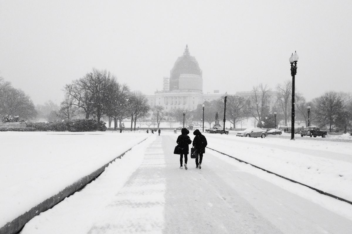 A snowy setting by the Capitol with two people walking by
