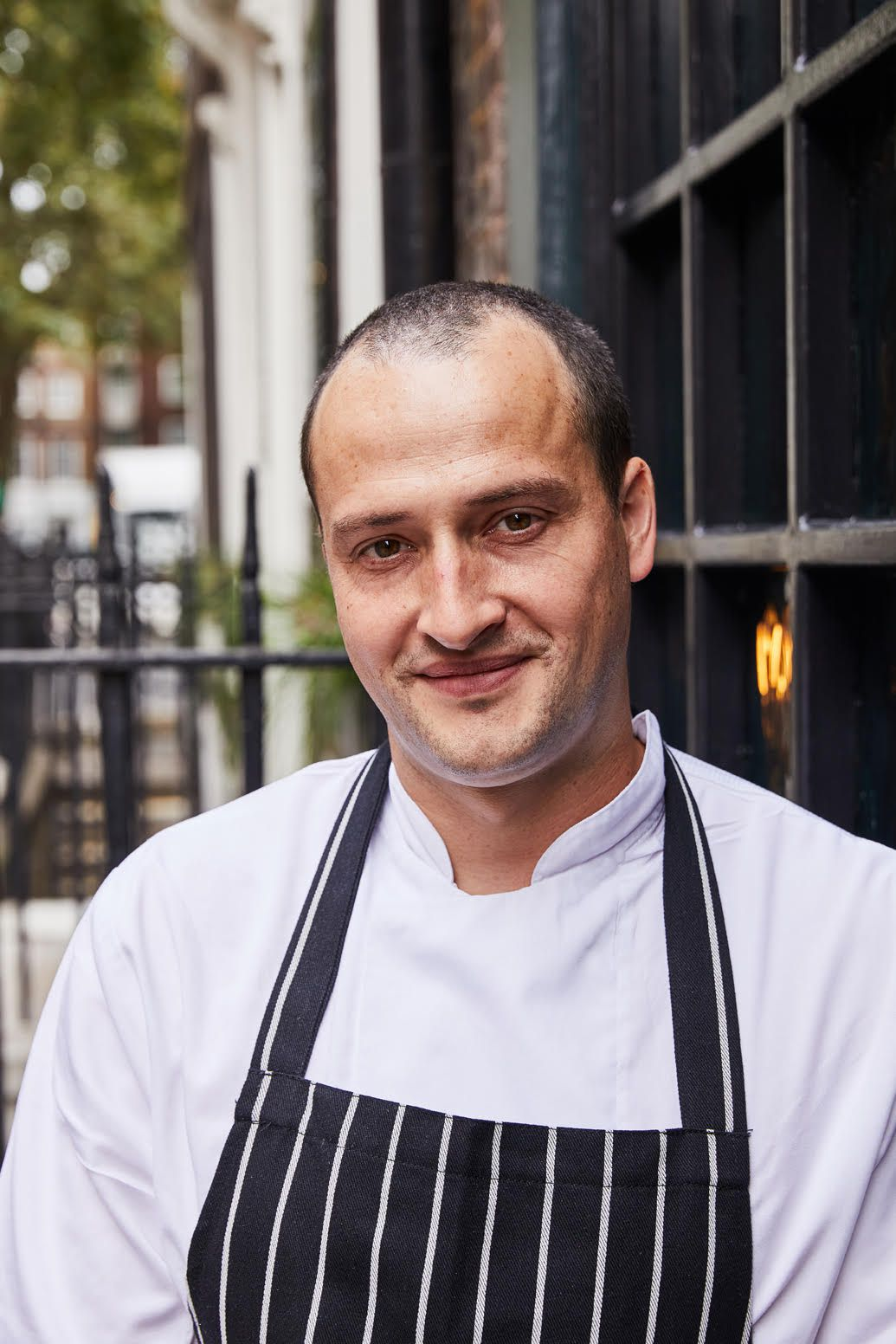 Chef Alex Jackson, in a blue and white striped apron and white shirt, outside Noble Rot restaurant in Soho