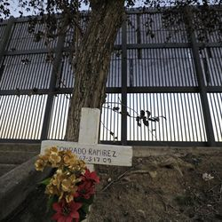 A view of a memorial cross and the border fence near Alice Wilson Memorial Park in Brownsville, Texas, on Monday, Feb. 22, 2021.