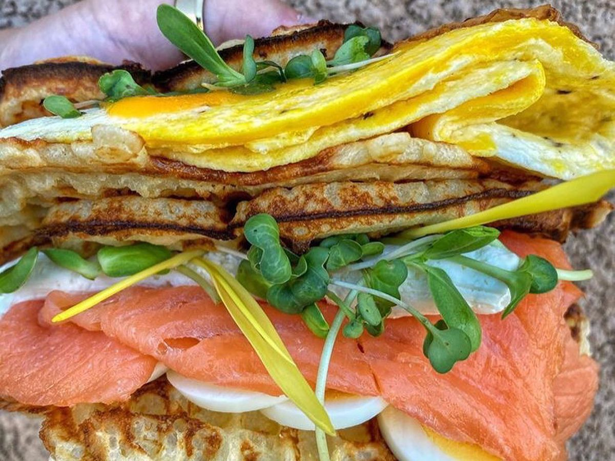 A waffle with eggs, salmon, and sprouts.