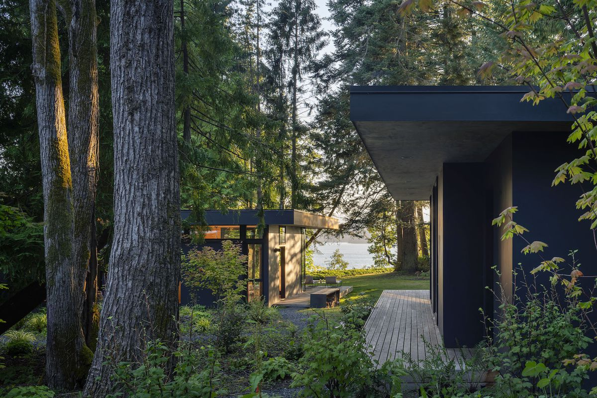 Two modern cabins with dark exterior sit in a wooded landscape.