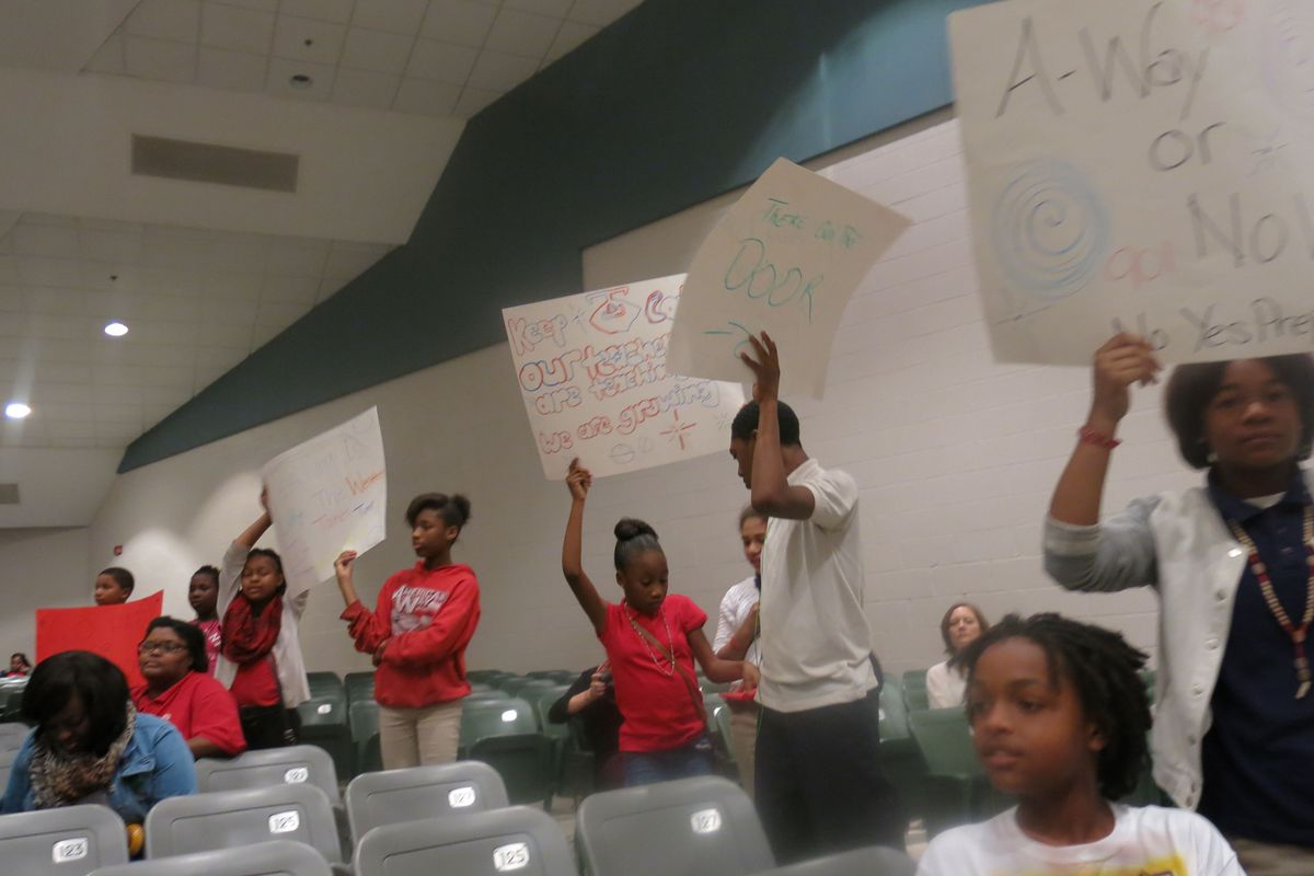 Several American Way students held signs during Monday night's school takeover community meeting with Yes Prep.