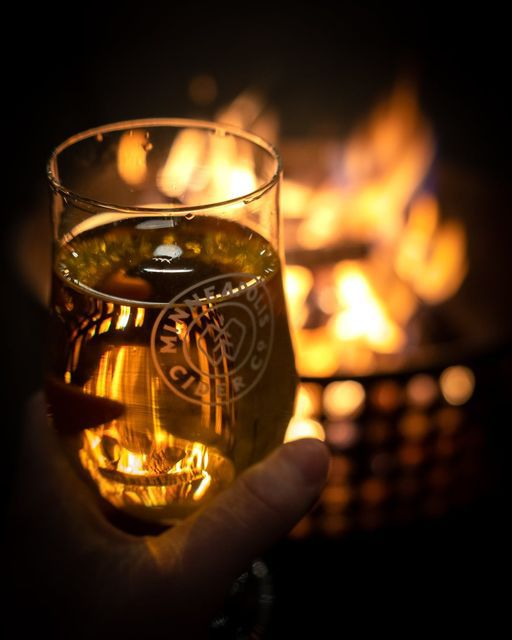 A mittened hand holds a full glass of golden cider beside a fire pit