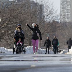Two women pushing along a stroller walk along the Lakefront Trail near Diversey Harbor, Tuesday, Feb. 23, 2021. The Chicago Parks District reopened the Lakefront Trail Tuesday.
