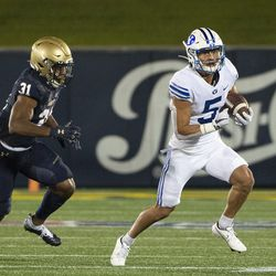 BYU's Dax Milne (5) runs after the catch as Navy linebacker Austin Talbert-Loving (31) defends during the first half of an NCAA college football game, Monday, Sept. 7, 2020, in Annapolis, Md.
