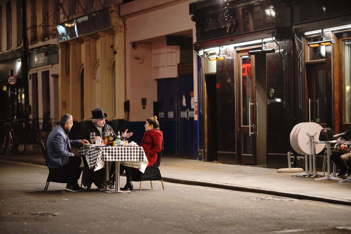 A lone restaurant table on a Soho street, with a couple dining as a man in a tuxedo crouches down next to them — the street is otherwise empty, and it is dark but for streetlights