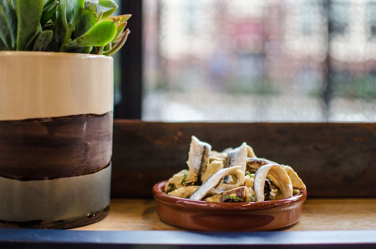 A small brown plate is full of fried artichokes and anchovies. It sits on a wooden windowsill next to a flowerpot.