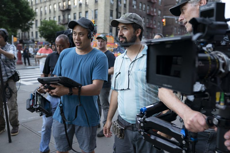 Two men stand near film cameras.