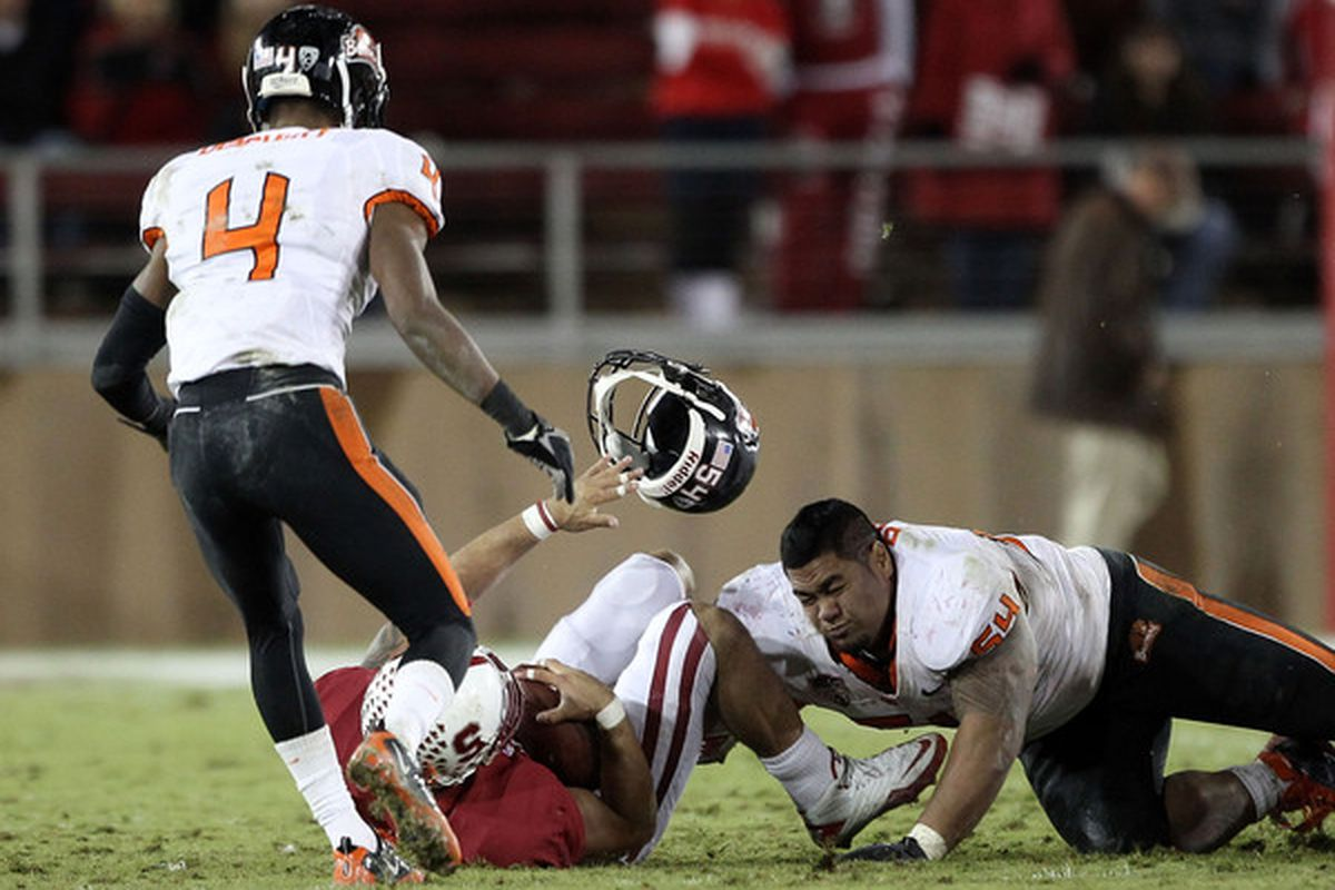 That is Stephen Paea #54 of the Oregon State Beavers on the right.  He is strong like a bull.