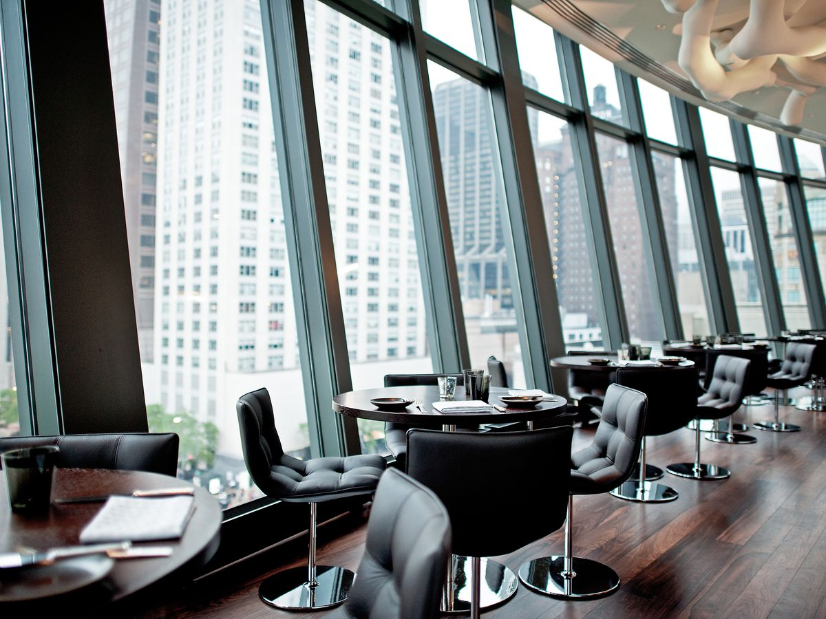 A restaurant's dining room full of windows that show downtown Chicago skyline views.
