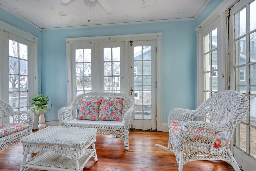 A closed in porch with furniture and large windows.