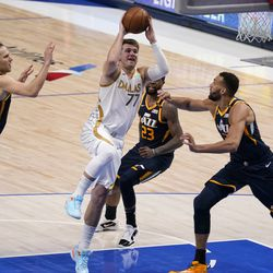 Dallas Mavericks guard Luka Doncic (77) leaps to the basket for a shot as Utah Jazz's Bojan Bogdanovic (44), Royce O'Neale (23) and Rudy Gobert, right, defend in the second half of an NBA basketball game in Dallas, Monday April 5, 2021.