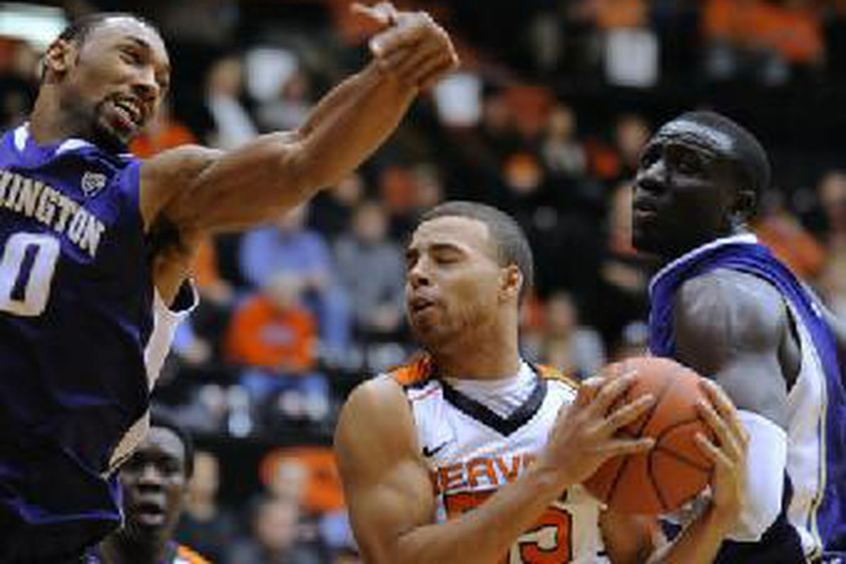 Oregon St.'s Roberto Nelson battles his way to a rebound between Washington's Desmond Symonds and Aziz N'Diaye. The Beavers led the Huskies wire to wire, though it got close for a while.