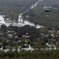 In this aerial photo, a Louisiana National Guard helicopter carries a sandbag to drop in an unintentional levee breach as it flies over the floodwaters in the aftermath of Hurricane Isaac in Braithwaite, La., Wednesday, Sept. 5, 2012. Thousands of electric customers are still without power, hundreds remained in shelters and several miles of coast line was tarred with weathered oil washing ashore, days after Isaac raked Louisiana.