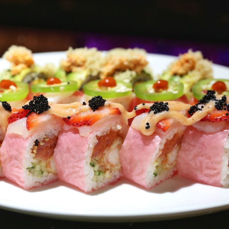 A selection of sushi rolls sit atop a white plate, backdropped by a black wall.