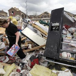 Ashley Quinton walks through the tornado damaged home of her friend Sherry Enochs in hopes of finding personal items that can be salvaged Wednesday, April 4, 2012, in Forney, Texas. Enochs was babysitting three children, all under the age of 3, that survived the storm with only minor bumps and scrapes.