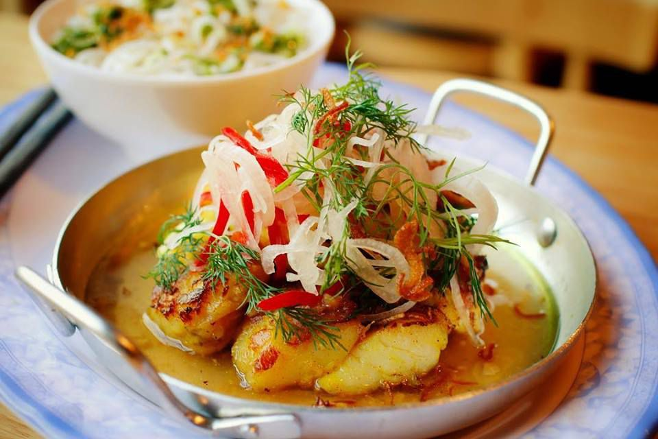 A small metal pan holds a colorful monkfish dish topped with green dill, pickled shallots, and fresno.