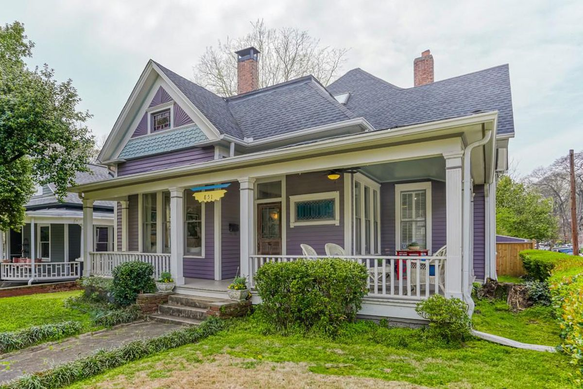 A purple and white Victorian house on a green lawn with trees to the left.