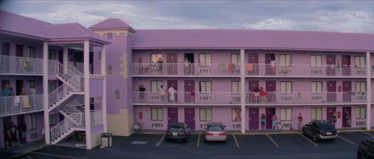 The purple-tinted motel with guests all standing on the balcony