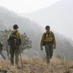 In this June 2, 2012 file photo, firefighters from the Granite Mountain Hotshots of Prescott, Ariz. cut a fire line along a mountain ridge in the Gila National Forest outside Mogollon, N.M. On Sunday, June 30, 2013, a fast-moving wildfire killed 19 firefighters from this group after the blaze raced through the central Arizona town of Yarnell, about 85 miles northwest of Phoenix. (AP Photo/U.S. Forest Service, Tara Ross)