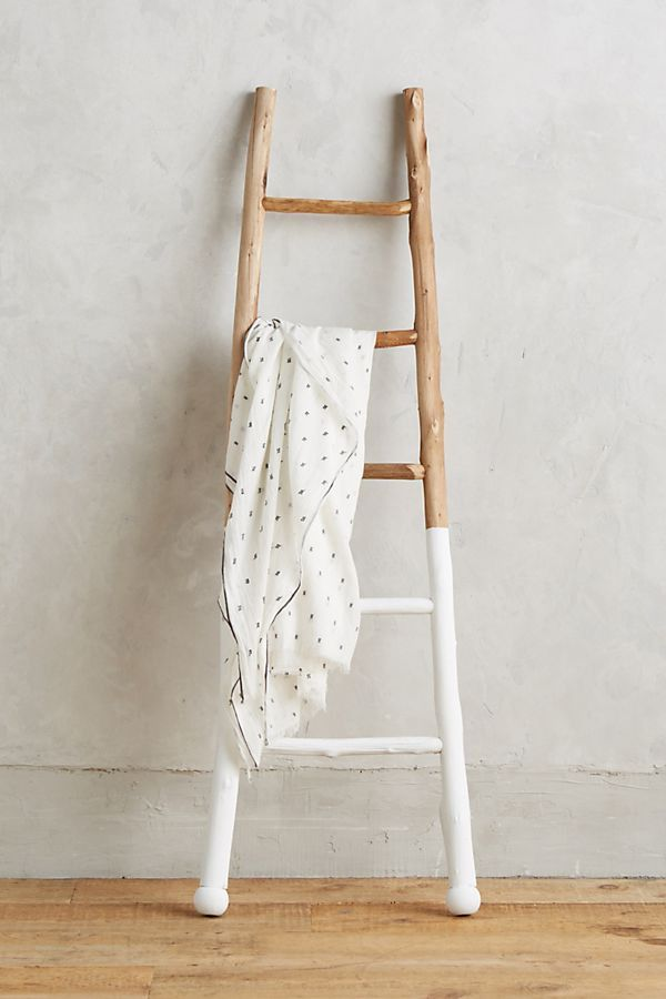 Wooden ladder with the bottom half dipped in white paint.
