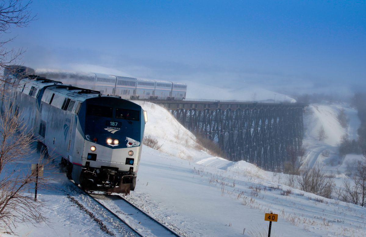 A train rides on a track through a snowy landscape.