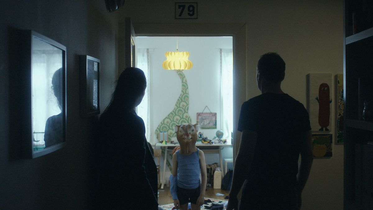 A child wearing a rat head costume stands in a hallway flanked by two adults in silhouette.