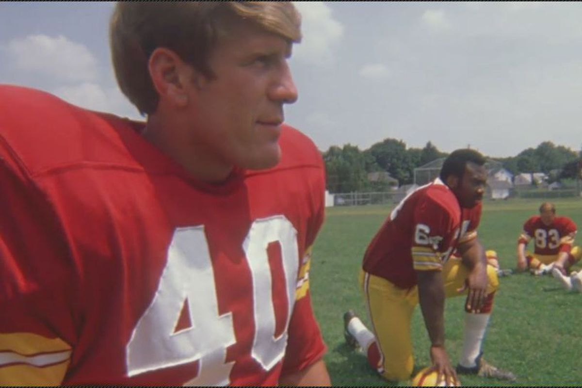 Dave Kopay stands to the left in his Washington Football Team jersey.