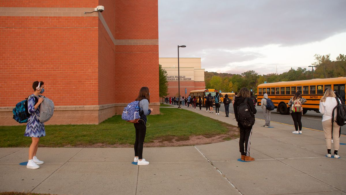 Students line up on socially distanced dots painted on the sidewalk to wait their turn to be scanned by a temperature screener before classes at Middletown High School.