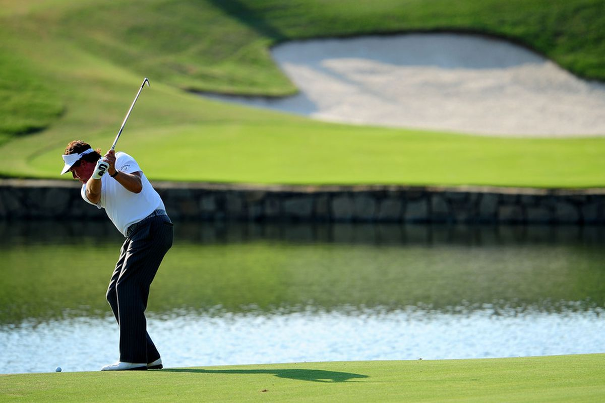 JOHNS CREEK, GA - AUGUST 12:  Phil Mickelson hits an approach shot on the 18th hole during the second round of the 93rd PGA Championship at the Atlanta Athletic Club on August 12, 2011 in Johns Creek, Georgia.  (Photo by Stuart Franklin/Getty Images)