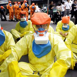 South Korean participants wear anti-chemical, biochemical and radiological cloth and masks during an anti-terrorism exercise at Samsung Electronic's building in Seoul, South Korea, Tuesday. North Korea's decision to restart tours run jointly with South Korea and allow reunions of families separated for decades by the peninsula's war is aimed at obtaining much-needed foreign currency and leverage in negotiations with Washington and Seoul, experts said.