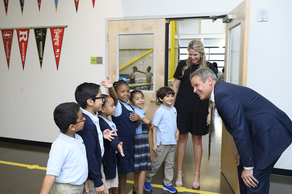 Man in a suit bends down to talk to six elementary students lined up outside a room.