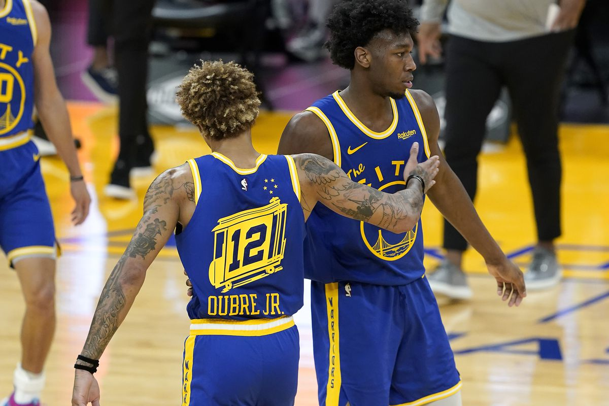Kelly Oubre Jr. and James Wiseman of the Golden State Warriors gets together after a timeout called by the Utah Jazz during the second half of an NBA basketball game at Chase Center on March 14, 2021 in San Francisco, California.