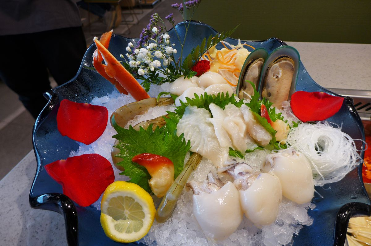 Many types of seafood are displayed on ice, with rose petals strewn here and there...