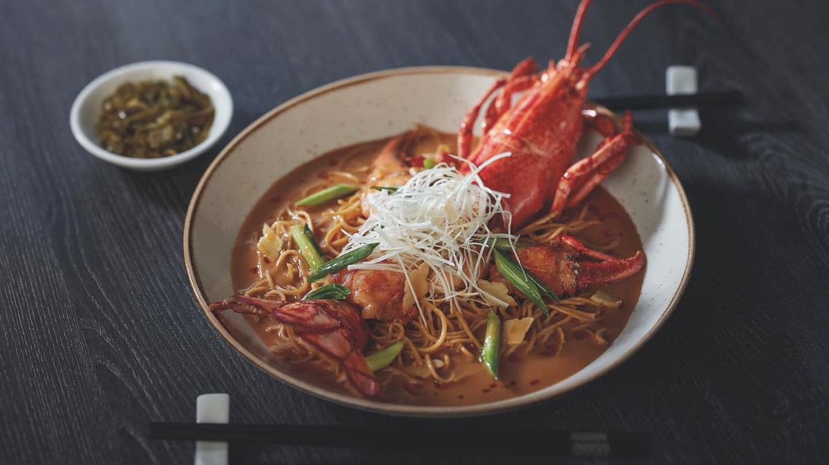 A lobster in a bowl with a noodle soup surrounding it.